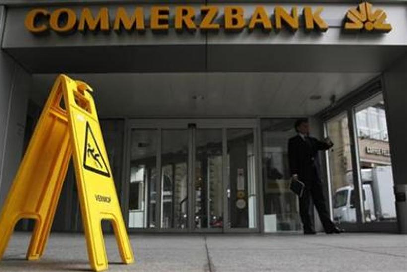 A man looks at his watch outside a branch of Commerzbank in Frankfurt