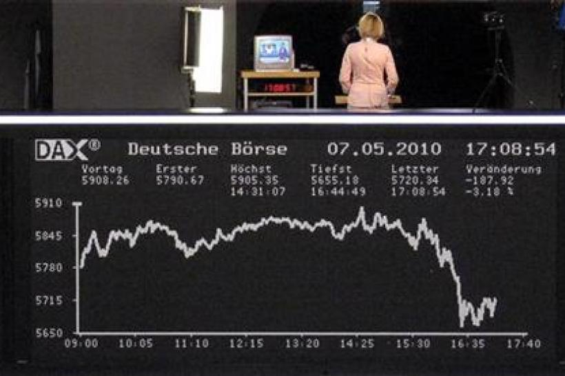 A woman stands on the balcony above of the DAX board at the Frankfurt stock exchange