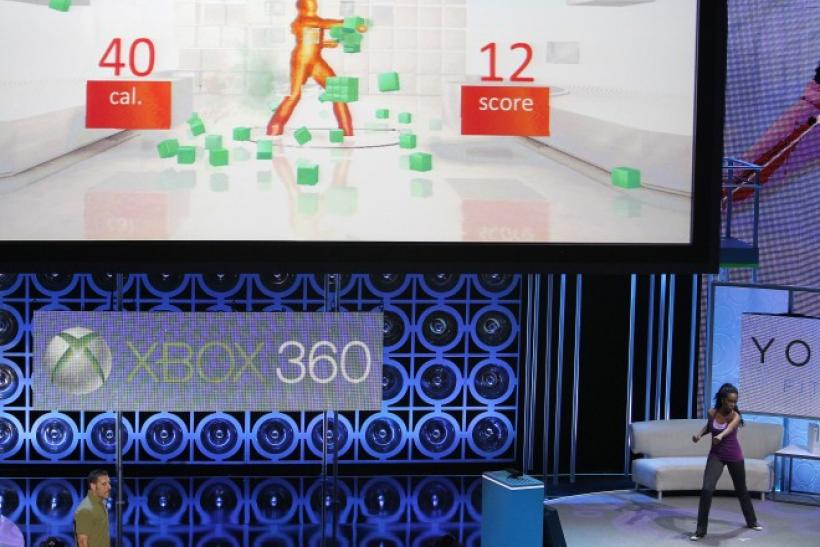 "An assistant demonstrates the game ""Your Shape: Fitness Evolved"" for Kinect for Xbox 360 during a media briefing in Los Angeles."