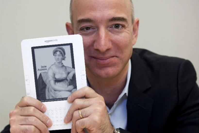 Jeff Bezos, CEO of Amazon.com Inc., shows a Kindle in Cupertino, California