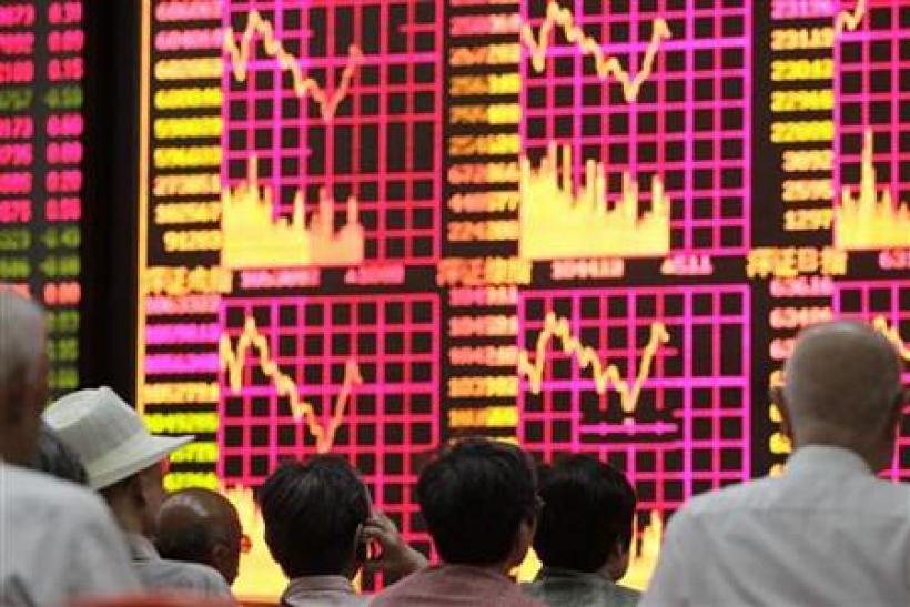 People look at an electronic board at a brokerage house in Shanghai