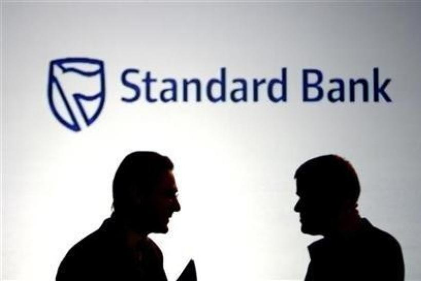 Businessmen chat in front of a Standard Bank logo in Sandton outside Johannesburg