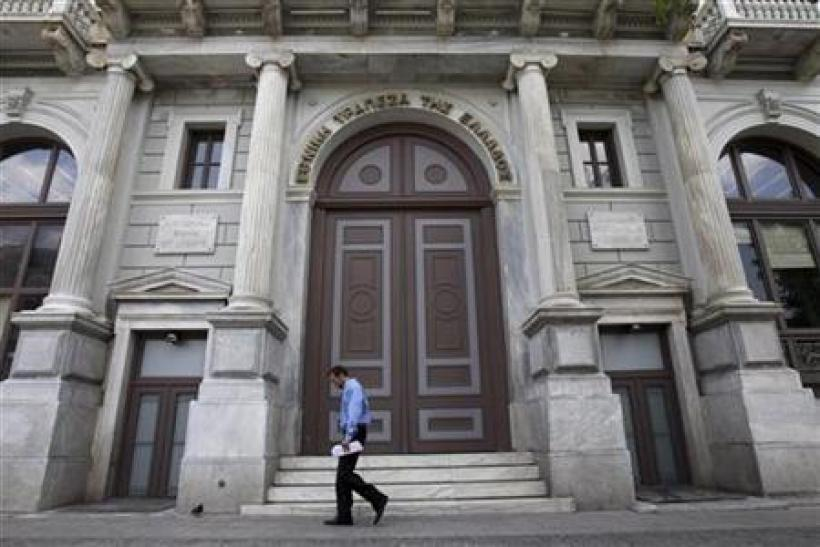 A man walks in front of the headquarters of National Bank of Greece in Athens