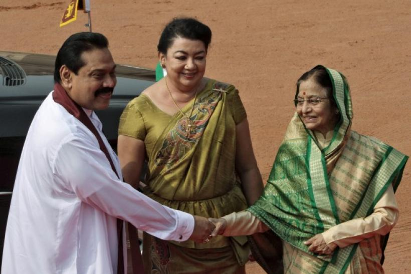 Sri Lanka's President Rajapaksa shakes hands with his Indian counterpart Patil as his wife Shiranthi watches