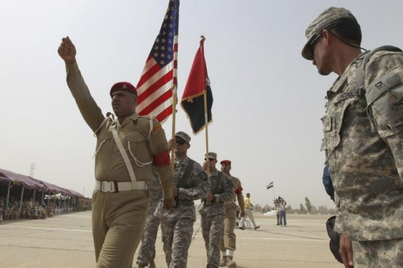 U.S. soldiers from the 4th Stryker Brigade 2nd Infantry Division carry flags during a departure ceremony of U.S. Forces, at Abu Ghraib in Baghdad, August 7, 2010.