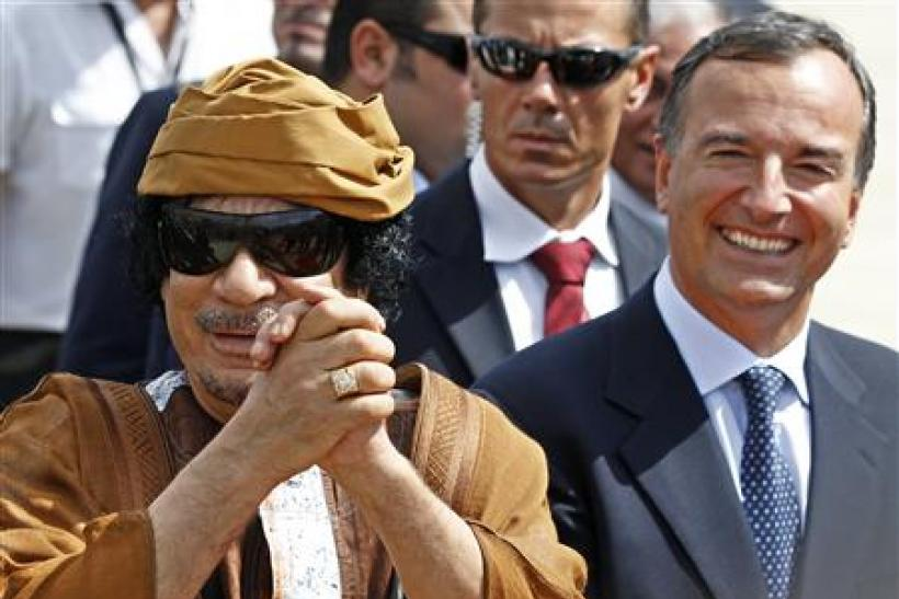 Libyan leader Gaddafi gestures next to Italian Foreign Minister Frattini at the Ciampino airport in Rome