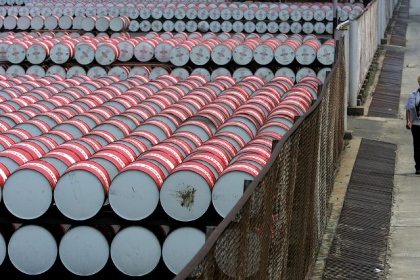 Oil company Pertamina employee walks beside oil drums at oil pump station, Jakarta.