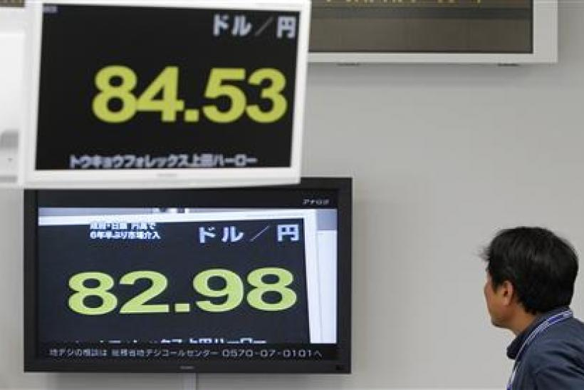 A foreign exchange broker watches a television showing the Japanese yen's exchange rates against the U.S. dollar in this file photo.