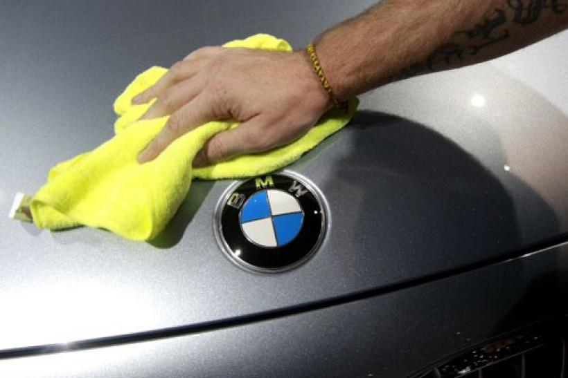 An employee cleans a BMW car displayed on media day at the Paris Mondial de l'Automobile (Paris Auto Show) October 1, 2010