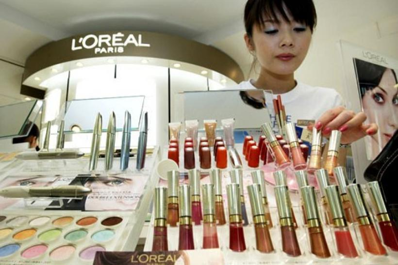A beauty consultant adjusts cosmetics displayed at L'Oreal Paris' counter at a department store in Tokyo