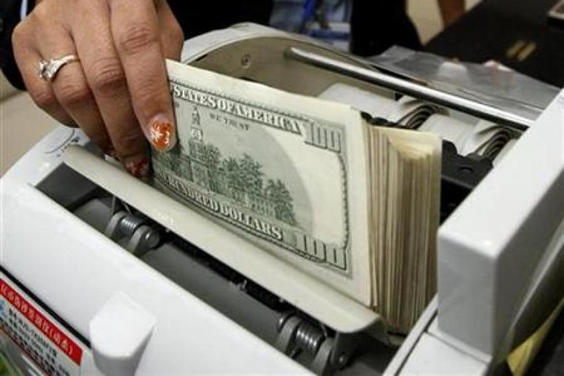An employee counts U.S. dollars at ACLEDA bank in Phnom Penh