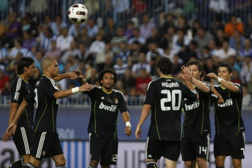 Real Madrid's Higuain is congratulated by his team mates after scoring his second goal against Malaga during their Spanish First Division soccer match in Malaga