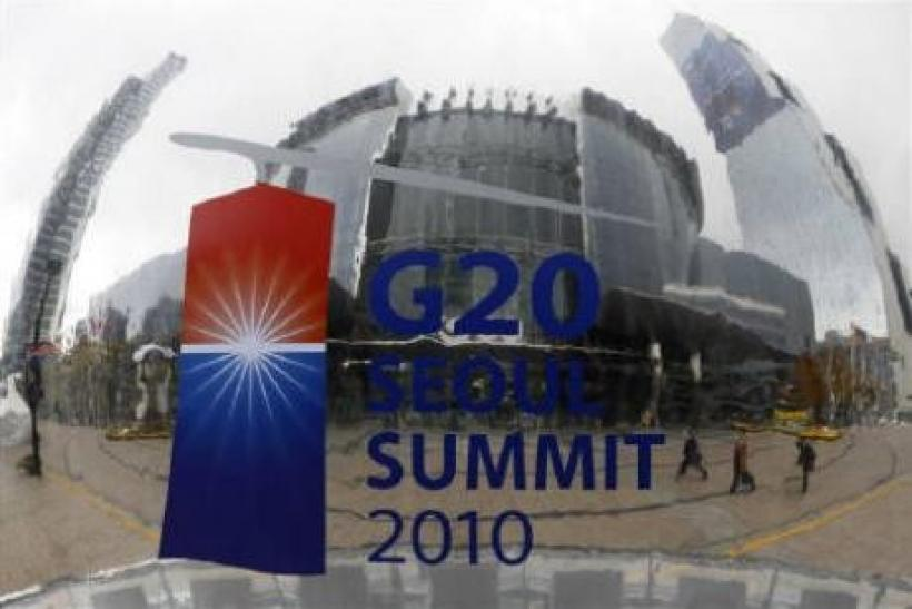 People are reflected on a sculpture in front of the Coex Convention Centre, the venue of the G20 summit, in Seoul November 8, 2010.