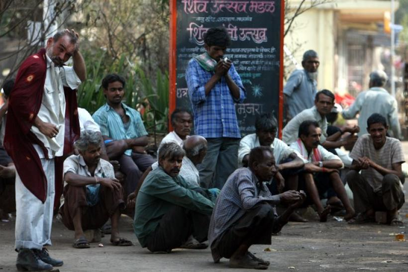 Daily wage workers wait for employment on a street side at an industrial area in Mumbai
