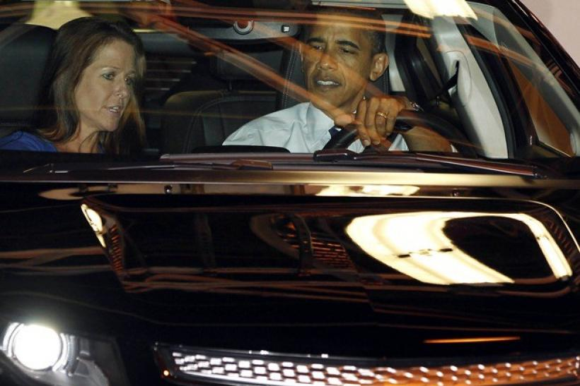 U.S. President Barack Obama sits next to plant manager Teri Quigley (L) as he drives a Volt car off the assembly line at a General Motors Auto Plant in Hamtramck, Michigan, near Detroit, July 30, 2010.