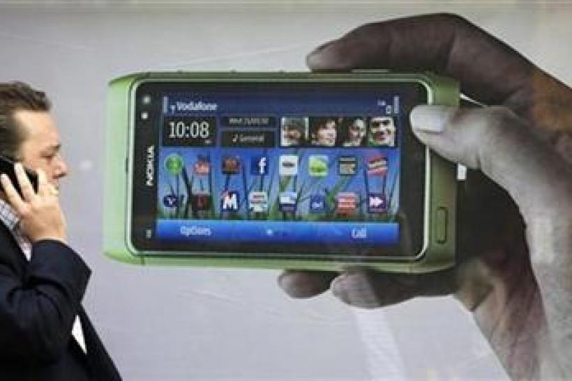 A man talks on his mobile phone as he walks past an advertisment for the new Nokia N8 on Oxford Street in London