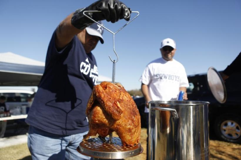 Mike Damian (L) pulls his Thanksgiving day turkey out of the frier before the start of an NFL football game between the Dallas Cowboys and Oakland Raiders in Arlington, Texas