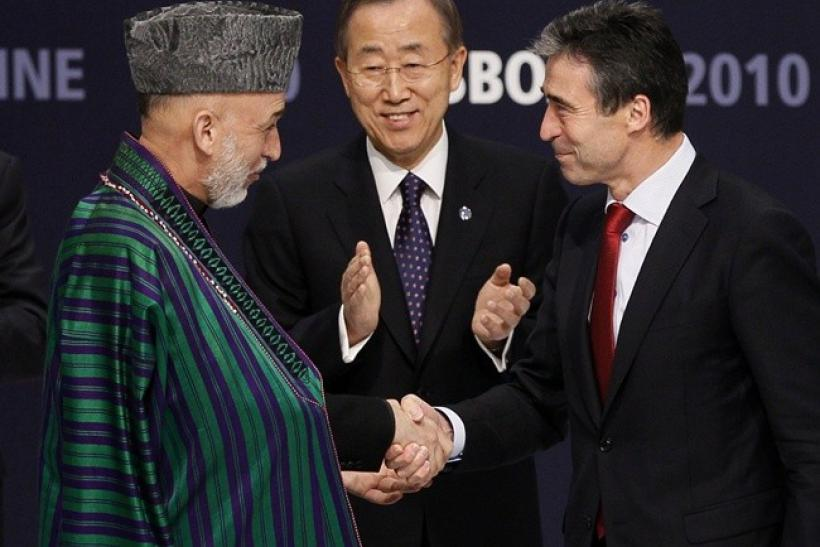 Afghanistan's President Hamid Karzai (L) and NATO Secretary General Anders Fogh Rasmussen (R) shake hands in front of U.N. Secretary General Ban Ki-moon after signing accords during the NATO Summit in Lisbon November 20, 2010.