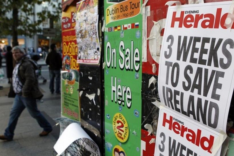 A man walks past newspaper headlines posted on a news stand on O'Connell street, Dublin, November 19, 2010. A financial aid plan to help Ireland cope with its battered banks will be unveiled next week, EU sources said on Friday, but experts warned a rescu