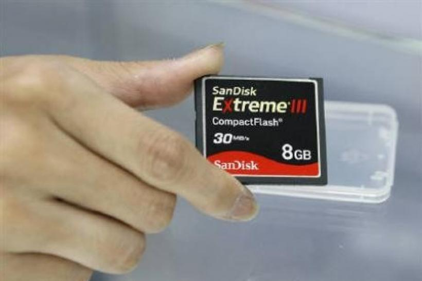 An employee of a computer shop poses with a SanDisk compact flash memory card