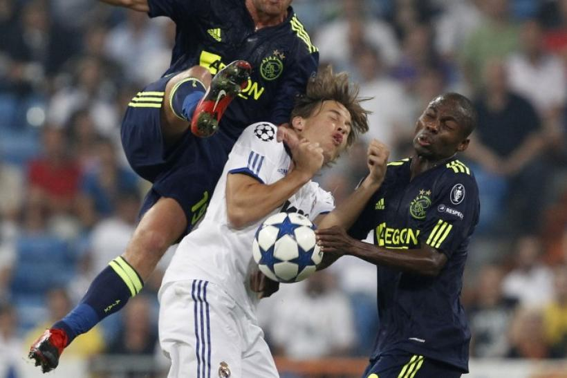 Real Madrid's Canales is challenged by Ajax's Tainio and Enoh during their Champions League soccer match in Madrid