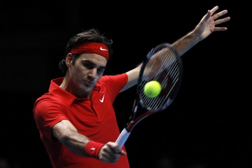 Switzerland's Roger Federer returns the ball to Britain's Andy Murray in their singles match at the ATP World Tour Finals in London.