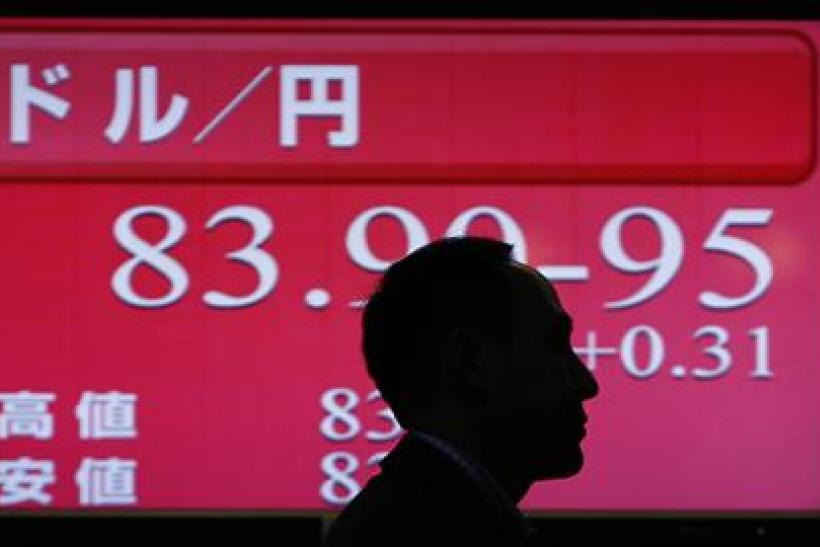 Man walks past an electronic board displaying the Japanese Yen's exchange rate against the U.S. dollar in Tokyo
