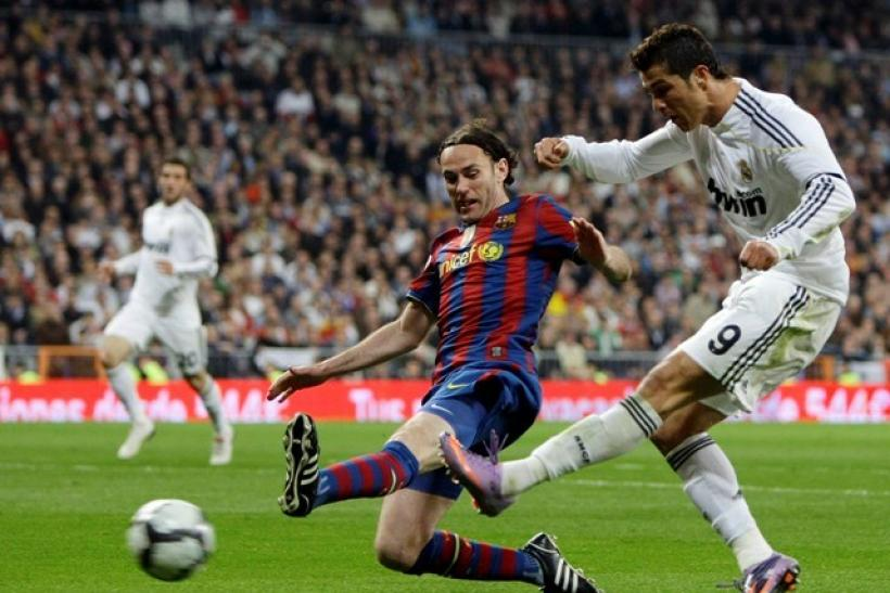 Real Madrid's Cristiano Ronaldo (R) kicks the ball past Barcelona's Gabi Milito during their Spanish first division soccer match at Santiago Bernabeu stadium in Madrid April 10, 2010.