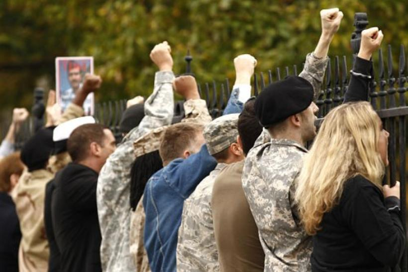 "In an act of civil disobedience, demonstrators handcuff themselves to the fence at the White House and shout their protests against the military's ""don't ask, don't tell"" policy in Washington November 15, 2010"