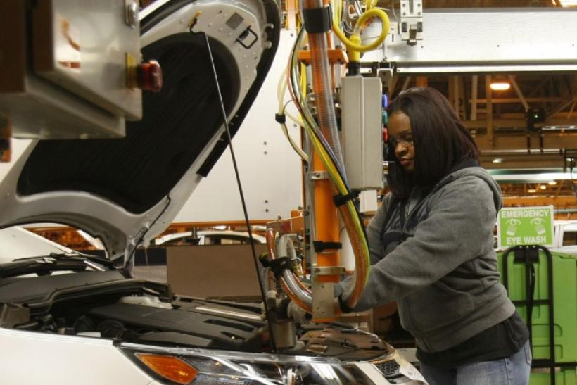 A General Motors assembly worker works on the battery installed in a 2011 Chevrolet Volt electric vehicle at the Detroit-Hamtramck Assembly plant in Hamtramck, Michigan