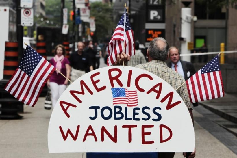 "A man holds a sign reading ""American Jobless Wanted"" on the street ahead of the G20 summit in Toronto"