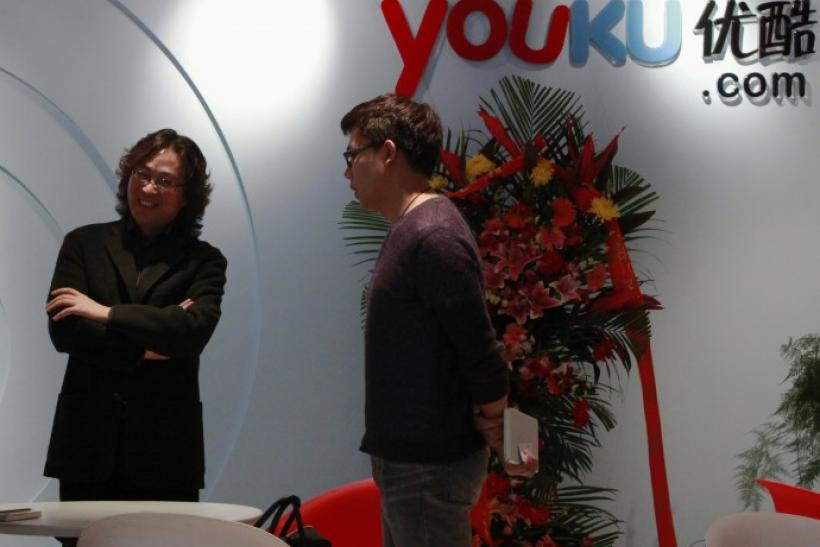 A client speaks to an employee next to the logo of Youku.com at the company's headquarters in Beijing
