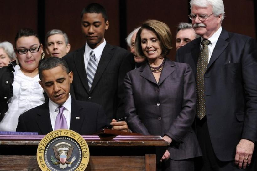 House Speaker Nancy Pelosi (D-CA) (2nd R) and Rep. George Miller (D-CA) (R) look on as U.S. President Barack Obama signs the Health Care and Education Reconciliation Act into law at Northern Virginia Community College in Alexandria, Virginia, March 30, 20