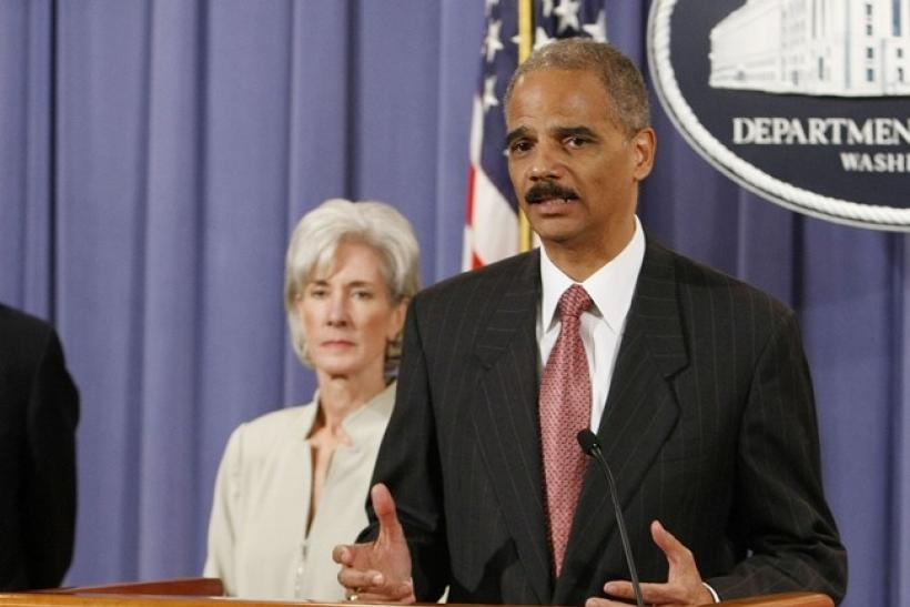U.S. Attorney General Eric Holder (R) discusses the Healthcare Fraud and Prevention and Enforcement Action Team (HEAT) at the Justice Department in Washington, June 24, 2009. U.S. Secretary of HHS Kathleen is seen in the background.