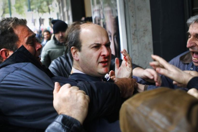 "Former conservative minister Kostis Hatzidakis reacts after being attacked by leftists with their fists, stones and sticks, while they shouted: ""Thieves! Shame on you!"" during a march against austerity measures in central Athens"