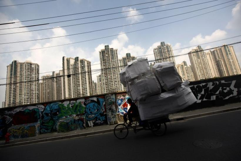 A man rides his tricycle past a residential site in Shanghai