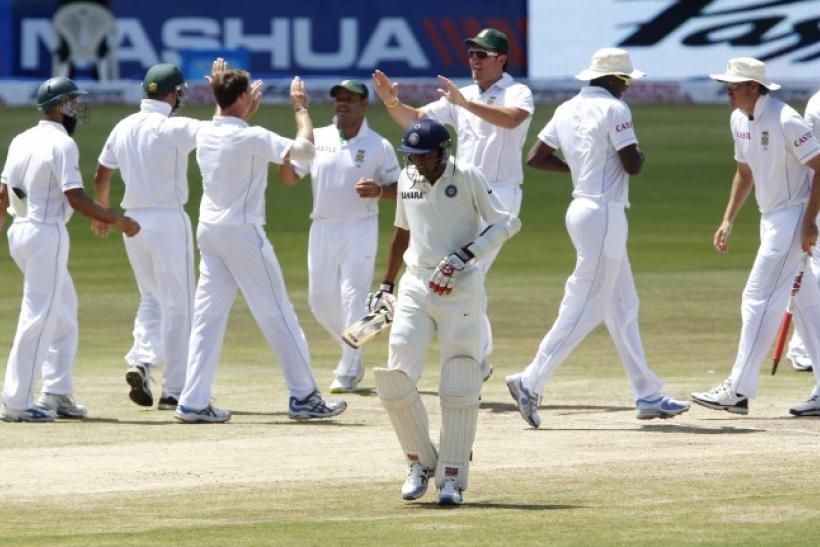 India's Unadkat walks off the field as South Africa's players celebrate his dismissal during their first test cricket match in Pretoria.