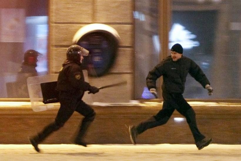 A riot policeman chases an opposition protester in Minsk