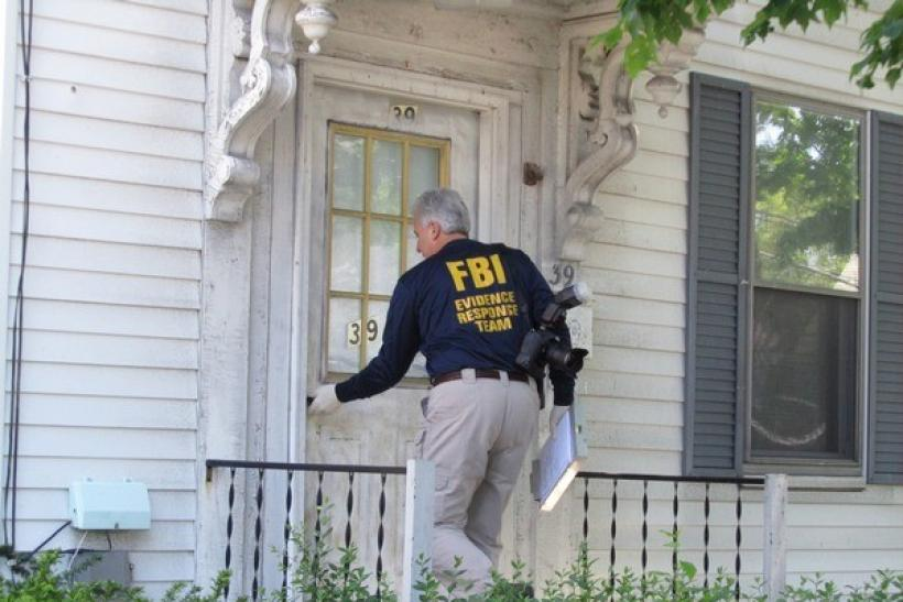 An FBI agent enters a house where a suspect was taken into federal custody earlier in the day, in Watertown, Massachusetts May 13, 2010.