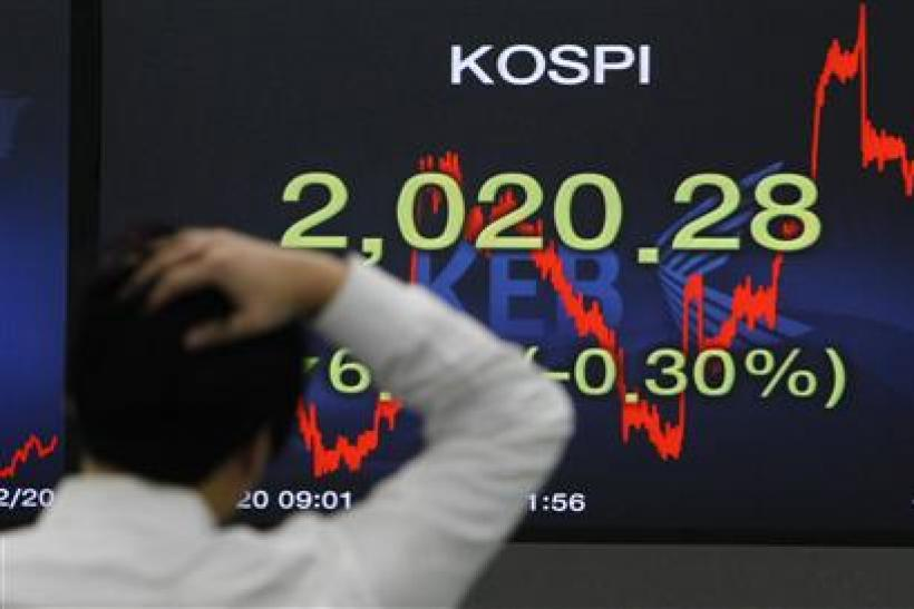 A foreign currency dealer walks past a screen displaying the Korea Composite Stock Price Index (KOSPI) at a bank in Seoul