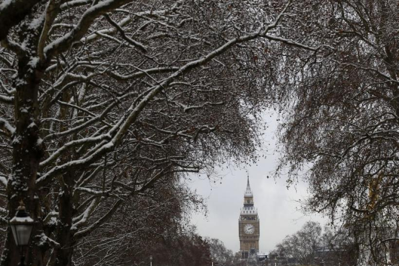 The Houses of Parliament are seen through snow covered trees in London