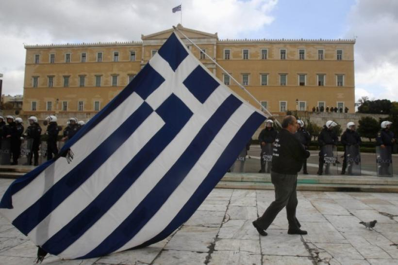 A striker parades with a huge Greek flag in front of riot police guarding the parliament in central Athens