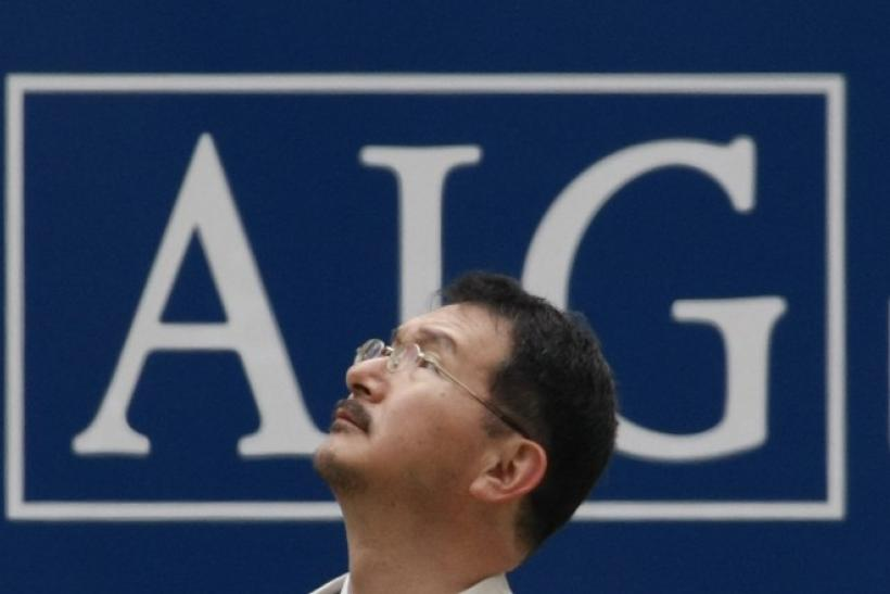 A man stands in front of an AIG logo in Tokyo