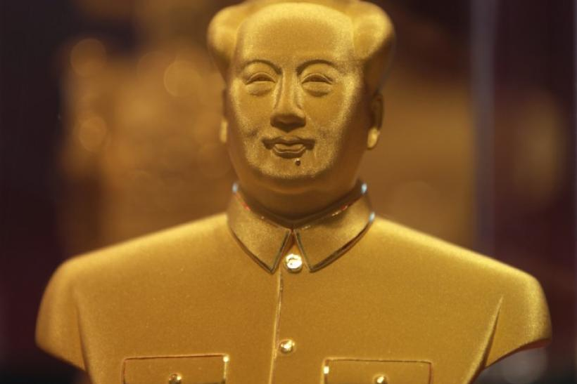 A golden statue of the late Chairman Mao Zedong is seen on display in a glass case at Caibai Ornaments store in Beijing