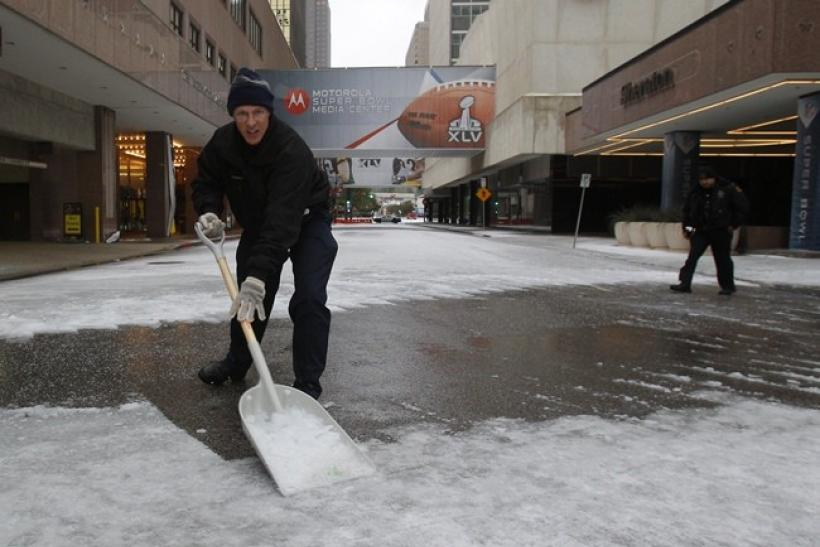 A hotel employee shovels snow from a street in front of a hotel housing news media after a storm front moved through Dallas, Texas, February 1, 2011. Super Bowl XLV is scheduled for February 6 at Cowboys Stadium in nearby Arlington, Texas.