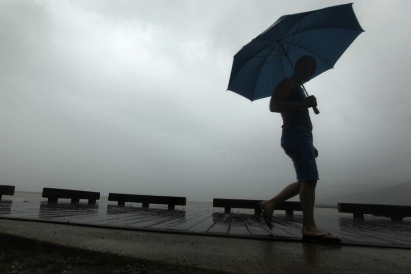 Sightseer walks along waterfront as he waits arrival of Cyclone Yasi in Cairns