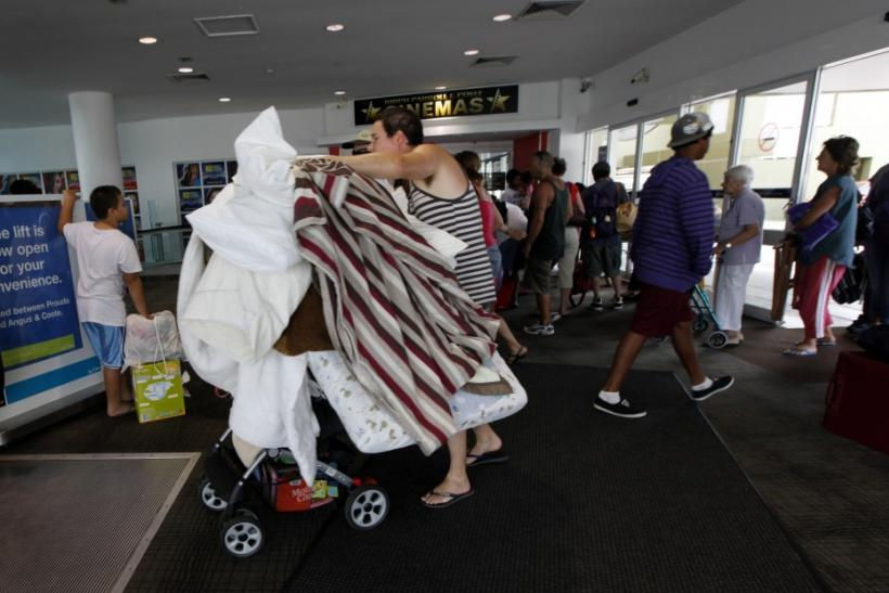 Man wheels bedding into an emergency cyclone shelter at a shopping mall in the northern Australian city of Cairns