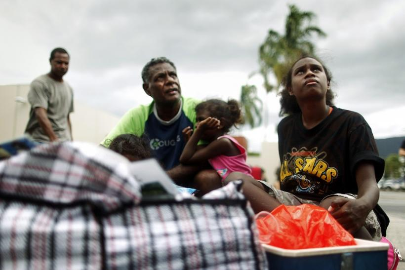 A resident and his daughter sit outside an emergency cyclone shelter after it was declared full and gate locked in the northern Australian city of Cairns