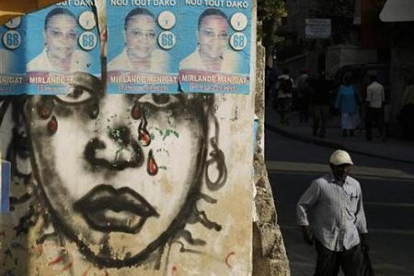 A Haitian man walks next to posters of Haiti's presidential candidate Mirlande Manigat in Port-au-Prince