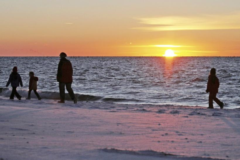 Tourists walk along the snow covered shore of the Baltic Sea island of Fehmarn